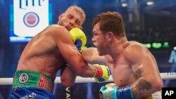 """El mexicano Saúl """"Canelo"""" Álvarez, asesta un puñetazo al británico Billy Joe Saunders, el sábado 8 de mayo de 2021, en una pelea por el cetro de los supermedianos, en Arlington, Texas (AP Foto/Jeffrey McWhorter)"""