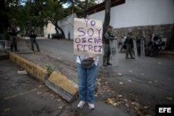 """Una mujer sostiene un cartel en el que se lee """"Yo soy Óscar Pérez"""" frente a la morgue en donde está cuerpo del exagente."""