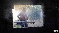 Un trabajador de la salud fumiga una casa para combatir el dengue en Cuba.