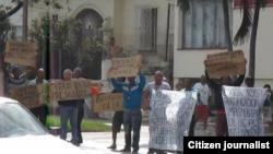 Imagen de los doce activistas protestando frente a la sede de la Asamblea Nacional del Poder Popular en el municipio Playa, Ciudad Habana.