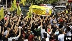Decenas de simpatizantes de Hezbolá portan el féretro con los restos de su camarada Saleh Ahmed Sabbagh, durante la celebración de su funeral en la ciudad de Sidón, al sur del Líbano,el miércoles 22 de mayo de 2013.