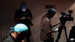 Periodistas con máscaras, guantes y gorros, como medida de prevención, cubren una conferencia en Caracas, el 4 de mayo de 2020.