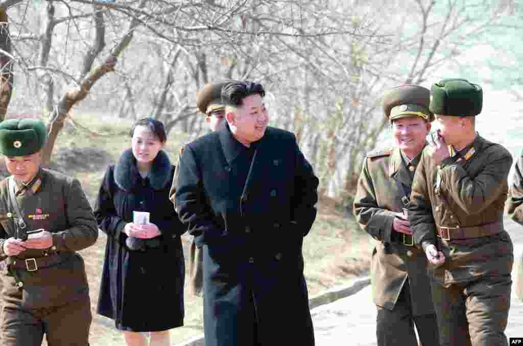 Esta imagen sin fecha publicada por la Agencia Central de Noticias de Corea del Norte (KCNA) el 12 de marzo de 2015 muestra al líder norcoreano Kim Jong-Un (C) inspeccionando la compañía de defensa Sin Islet en la provincia de Kangwon, en compañía de su h