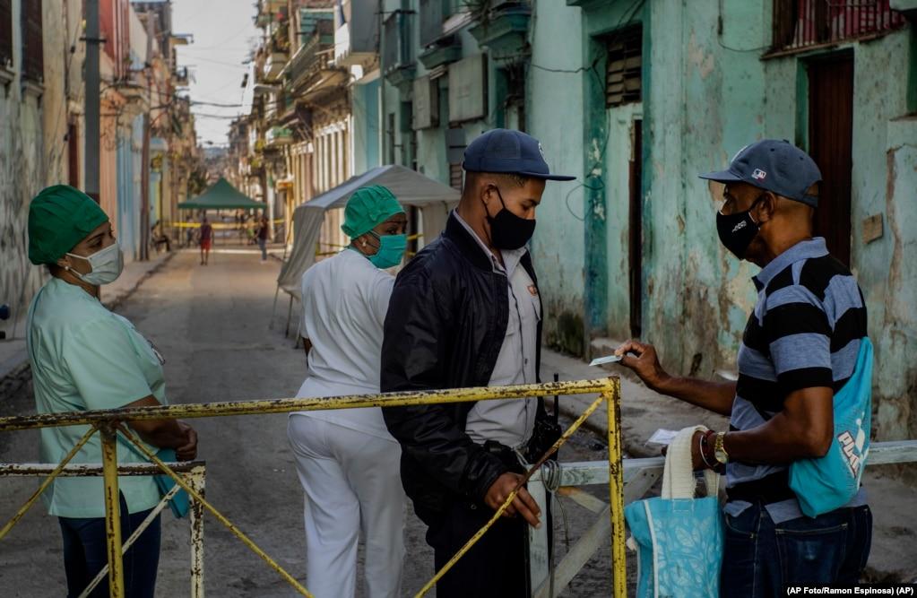 Ein Anwohner zeigt seinen Ausweis einem Polizeibeamten, der den Zugang zu einem Wohngebiet einschränkt, um die Ausbreitung des Coronavirus einzudämmen (22. Februar 2021). | Bildquelle: Radio Televisión Martí | Bilder sind in der Regel urheberrechtlich geschützt